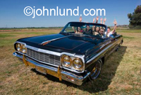Pic of hispanic friends piled into a classic vintage chevy impala in a green field in Northern California near Tracy.